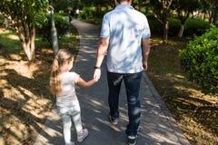 De papaholding overhandigde dochter met liefde en het lopen in het park Het concept van de familie royalty-vrije stock foto's