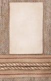 De papier âgé avec renvoyer le ruban et la corde sur la toile de jute Photographie stock libre de droits