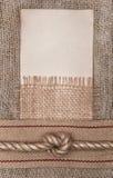 De papier âgé avec renvoyer le ruban et la corde sur la toile de jute Images libres de droits