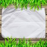 De papier chiffonné sur l'herbe verte avec du bois Photos libres de droits