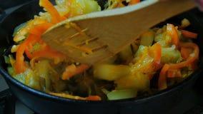 De paprika wordt toegevoegd aan de plantaardige schotel, bewegend met houten lepels stock video