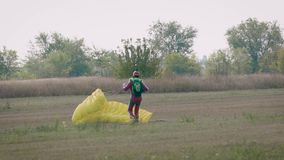 De parachutist is geland op gebied en het verminderen van zijn valscherm op grond na vlucht, in de zomerdag stock video