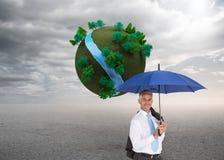 De paraplu die van de zakenmanholding bij camera glimlachen Royalty-vrije Stock Foto