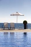 De paraplu en de stoelen van de zon dichtbij een pool Royalty-vrije Stock Afbeeldingen