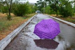 De paraplu ligt in de regen in de steeg Stock Foto