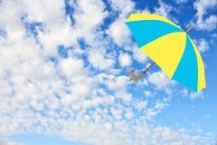 De paraplu in Oekraïense vlag kleurt vliegen in hemel tegen van zuiver w stock afbeelding