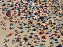 De paraplu's van de zon op een overvol strand stock fotografie