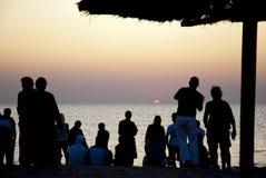 De paraplu's van het kuststrand bij zonsopgang en mensen die op de zonsopgang wachten Royalty-vrije Stock Afbeelding