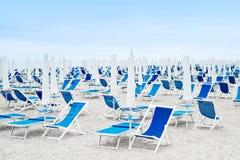 De paraplu's van het strand en blauwe deckchairs Royalty-vrije Stock Foto's