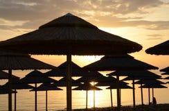 De paraplu's van het strandstro tegen de achtergrond van een dageraadhemel op de kusten van het Egeïsche Overzees stock afbeeldingen