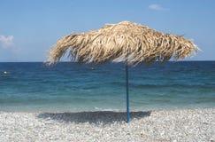 De paraplu's van het stro op het strand Stock Afbeeldingen