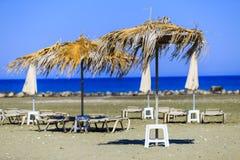 De paraplu's van de zonbescherming door de wind op het strand worden geblazen dat Royalty-vrije Stock Afbeeldingen