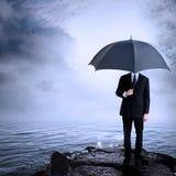De Paraplu van de Holding van de mens bij de Kust Royalty-vrije Stock Afbeeldingen