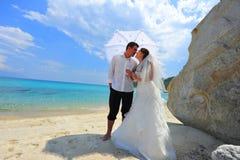 De paraplu van de liefde - jonggehuwdenpaar op exotisch strand Royalty-vrije Stock Afbeelding