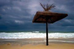 De paraplu van de zon die op een overstroomd strand wordt geïsoleerdm Royalty-vrije Stock Foto's