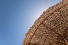 De paraplu van het met stro bedekkenen-dak en zuidelijke hemel Royalty-vrije Stock Foto's