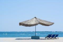 De paraplu van het strandstro van de zon op het strand met zonbedden, op de achtergrond van het overzees en de blauwe hemel, Stock Afbeelding