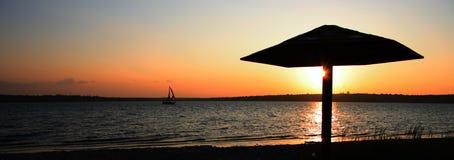 De paraplu van het stro bij zonsondergang stock afbeeldingen