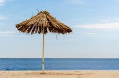 De paraplu van het strostrand op een lege kust op een duidelijke dag royalty-vrije stock afbeelding