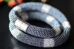De parel haakt halsband zwarte en zilveren kleuren op een donkere achtergrond Stock Afbeeldingen