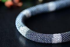De parel haakt halsband zwarte en zilveren kleuren op een donkere achtergrond Royalty-vrije Stock Afbeelding