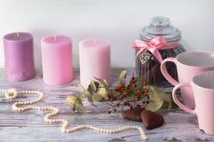 De parelhalsband, de kruik voor koekjes en twee roze koppen voor thee bevinden zich op lichtgrijze achtergrond Drie kaarsen en do Stock Afbeelding