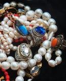 De de parelkettingen en ringen met colouresglas zoals Swarovsky kijken gehouden van als rubin en saffier Van India stock foto