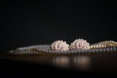 De parelsjuwelen plaatsten met schitterende grote die oorringen en verdubbelen tribunehalsband, elegant tegen een donkere achterg Royalty-vrije Stock Afbeeldingen