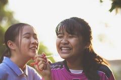 De paren van het Aziatische tiener ontspannen met soep borrelen tegen mooi zonlicht stock foto