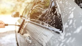 De partij van zilveren die auto in zelf wordt gewassen dient carwash, borstel door man hand wordt gehouden verlatend slagen in sh royalty-vrije stock fotografie