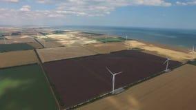 De partijenergie van de windmolensopbrengst tegen een mooi landschap Luchtonderzoek stock videobeelden