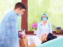 De partner helpt zijn vrouw tijdens de bevalling stock foto's