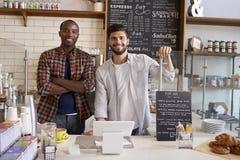 De partners bij de teller van een koffie winkelen omhoog, sluiten stock foto's