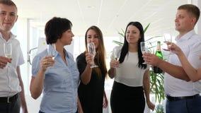 De partners die champagne drinken en maken clinking glazen op het werk in modern bureau stock videobeelden