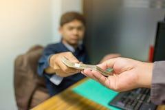 De partners leggen frauduleus contant geld aan ondernemers voor van wie mannelijke zakenlieden om steekpenningen in het bureau go stock foto