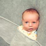 De pasgeboren baby is 9 dagen oude leugens die over een grijze achtergrond worden verpakt royalty-vrije stock foto