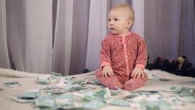 De pasgeboren baby kijkt als geld valt op hem stock footage