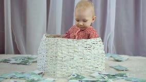 De pasgeboren baby kijkt als geld valt op hem stock video