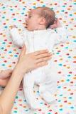 De pasgeboren baby kleedde zich in wit terug leggend op haar Royalty-vrije Stock Afbeelding