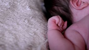 de pasgeboren baby ligt en beweegt zich met kleine handen stock videobeelden