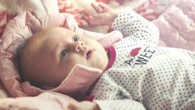 De pasgeboren baby ligt op zijn rug en probeert voor het eerst te glimlachen HD 1920x1080 stock video