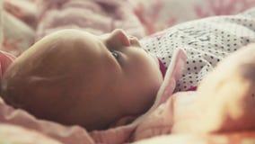 De pasgeboren baby ligt op zijn rug en probeert voor het eerst te glimlachen 1920x1080 HD stock video