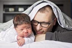 De pasgeboren baby van twee weken met vader in bed Royalty-vrije Stock Foto