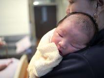 De pasgeboren baby wordt gehouden met handen van moeder stock foto