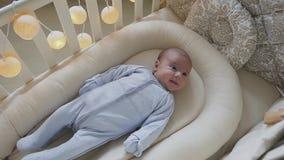 De pasgeboren babyjongen die in de voederbak liggen bekijkt camera en het glimlachen Leuk weinig baby die in de voederbak thuis l stock video