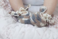 De pasgeboren babyvoeten sluiten omhoog in bruine gebreide sokkenbuiten op een witte deken De baby is in de voederbak royalty-vrije stock foto's