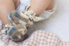 De pasgeboren babyvoeten sluiten omhoog in buiten van wol de bruine gebreide sokken op een witte deken De baby is in de voederbak royalty-vrije stock afbeelding