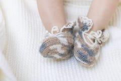 De pasgeboren babyvoeten sluiten omhoog in buiten van wol de bruine gebreide sokken op een witte deken De baby is in de voederbak stock foto