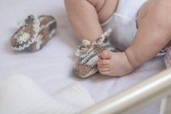 De pasgeboren babyvoeten sluiten omhoog in wolsokken op een witte deken De baby is in de voederbak ??n sok wordt verwijderd uit d royalty-vrije stock afbeelding