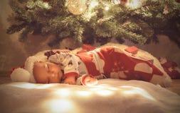 De pasgeboren die slaap van de babyjongen en het dromen onder Kerstmisboom bij de zak van slaapkerstmis wordt verpakt Stock Foto's
